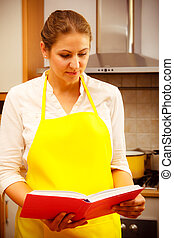 Housewife with cookbook in kitchen. - Mature housewife cook...