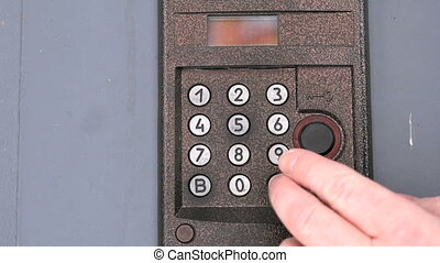 Person dialing number of apartment on a doorphone - The...