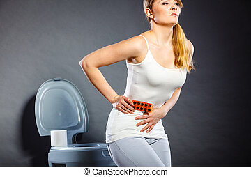 Woman suffer from belly pain holds pills in toilet -...