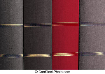 red book cover in stack of grey books - - red book cover in...