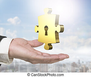 Man hand holding golden puzzle piece with keyhole - Man hand...