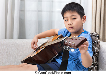 Asian Chinese little boy playing guitar on the sofa in the...