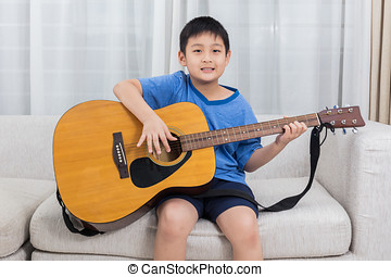 Happy Asian Chinese little boy playing guitar on the sofa in...