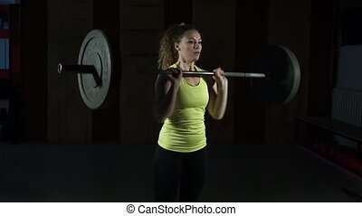 Young woman doing the taking barbell on the chest in the...