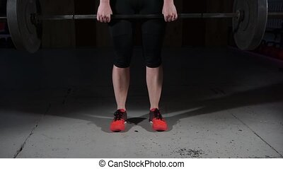 Young woman doing deadlifts with a barbell in the gym.
