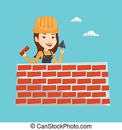 Bricklayer working with spatula and brick. - Young female...