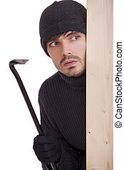 criminal guy with crowbar hiding behind wooden bar