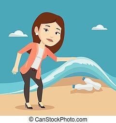 Woman showing plastic bottles under sea wave. - Caucasian...