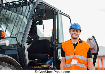 Construction worker with Skid Steer Loader in background