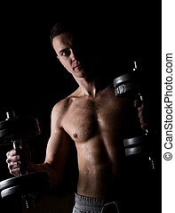 Handsome athletic man with dumbbell on a darck background.