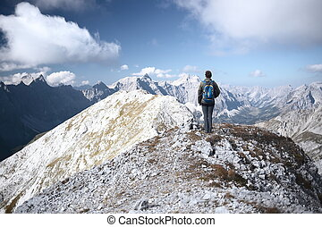 one mountain climber is standing on the top of a mountain