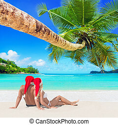 Romantic couple in red Christmas Santa hats sunbathe at...
