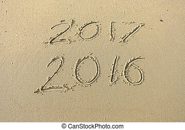 2016 2017 inscription written in the beach sand. Concept of celebrating the New Year