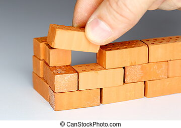 laying a brick - a hand is laying a brick to a wall