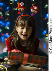 Girl Suprized by Christmas Gift Box - Young smiling girl...