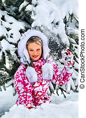 The child, a girl, happily playing in the snow. Snow-covered...
