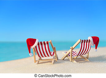 Two striped sunloungers with Christmas Santa hats at ocean...