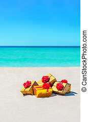 Gift boxes with big red bows on sandy sunny beach