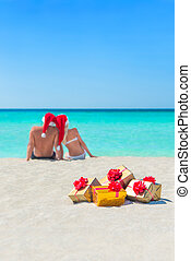 Golgen gifts and couple in Christmas Santa hats at beach -...