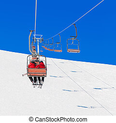 Chairlift transport skiers and snowboarders up slope at ski...