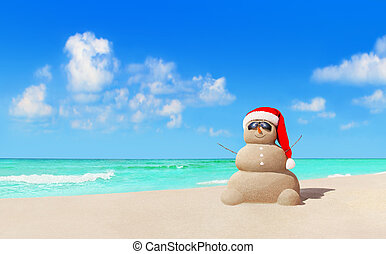 Sandy snowman in Christmas Santa hat and sunglasses at beach...