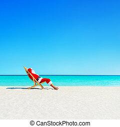 Christmas Santa Claus relaxing in sunlounger at ocean...