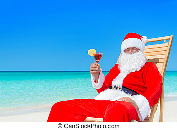 Christmas Santa Claus with cocktail on sunlounger at...