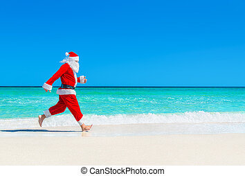 Christmas Santa Claus run at tropical beach against waves...