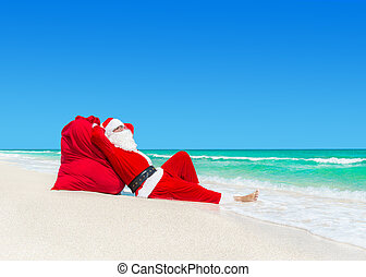 Santa Claus sunbathe on Christmas gifts sack at ocean beach...