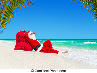 Santa Claus sunbathing on Christmas gifts sack at ocean palm...