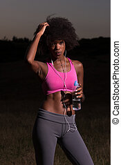 african american woman jogging in nature - portrait of a...