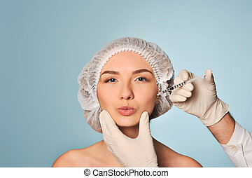 Attractive young woman gets cosmetic injection, isolated...