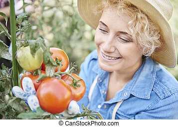 Blond woman holding bush of tomatoes