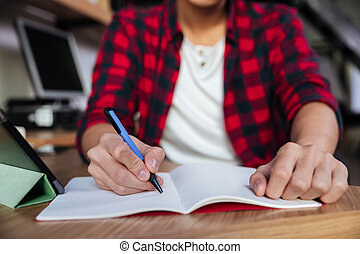Cropped image of asian male writing in notebook at library -...