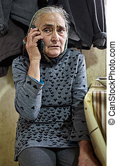 Old woman speaking on mobile phone - Old farmer woman indoor...