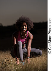 black woman runner tightening shoe lace - young African...