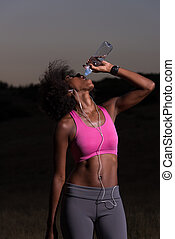 african american woman drinking water after jogging in...