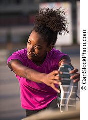 African American woman doing warming up and stretching -...
