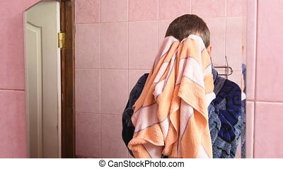 The young man wipes his face with a towel after washing