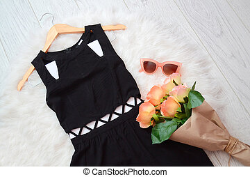 Fashion concept. Black dress and a bouquet of roses on a...