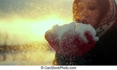 Winter portrait of a beautiful young woman blows snowflakes and smiling in slow motion during sunset time with lens flare effects. 1920x1080