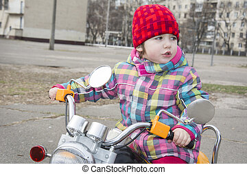 In the spring of a little girl riding a motorcycle on the...