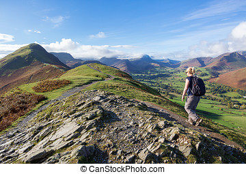 Walking Up Cat Bells in Cumbria, UK - A woman walking on the...