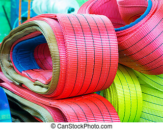 Colorful nylon soft lifting slings stacked in piles....