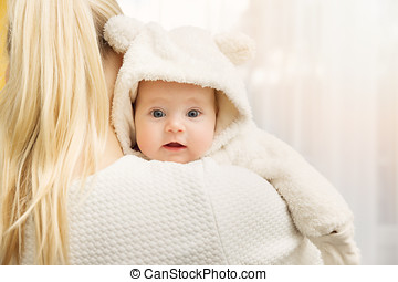 mother with her baby in fluffy bear costume over shoulder
