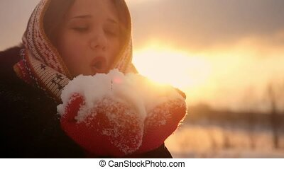 Beautiful young woman blows snowflakes and smiling in slow...