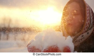 Winter portrait of a beautiful young woman blows snowflakes...