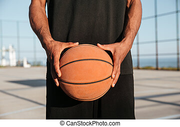 Portrait of male hands holding basketball with playground on background