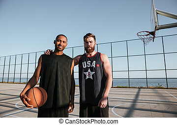 Basketball players standing together at the playground - Two...