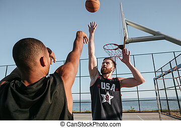 Two healthy basketball players at the playground outdoors